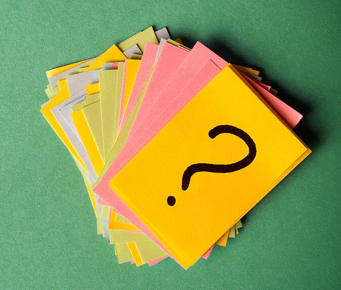 A set of coloured cards with a question mark drawn on the top